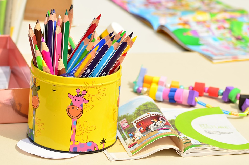 Coloured pencils on a desk full of crafts