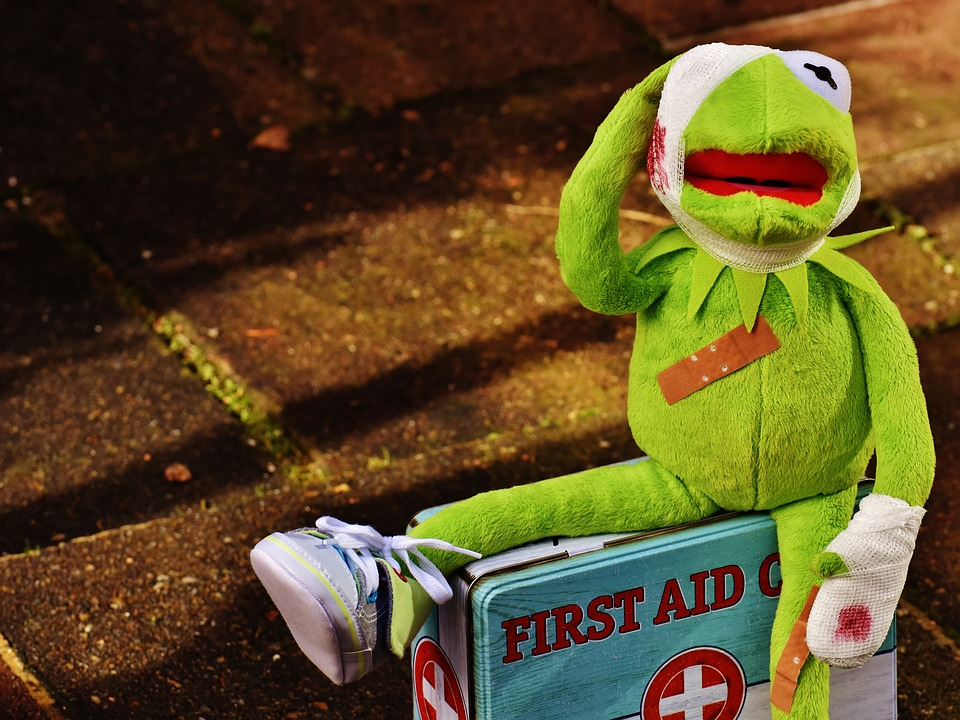 Kermit the frog bandaged up sitting on a first aid box