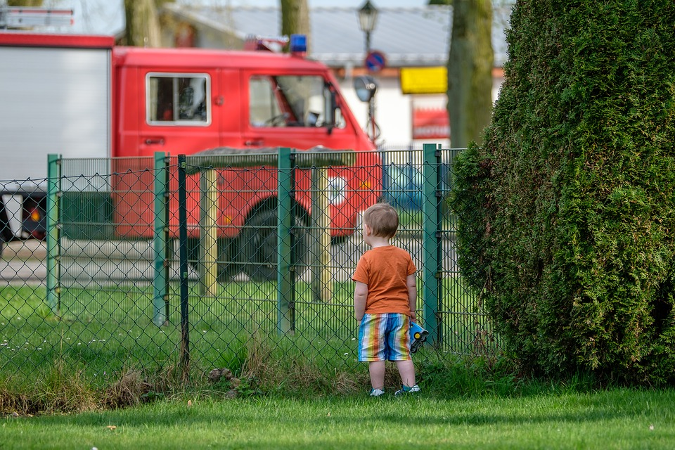 A little boy in a garden looking at a fire engine