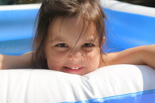A little girl leaning on the side of a paddling pool