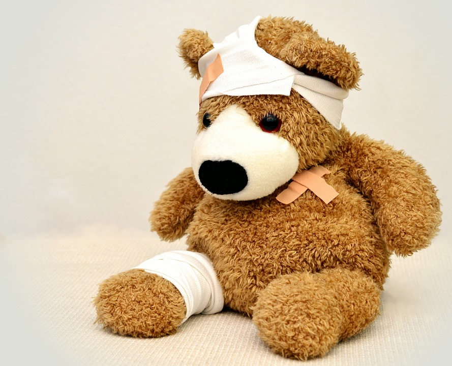 A teddy bear with bandages around his head and foot